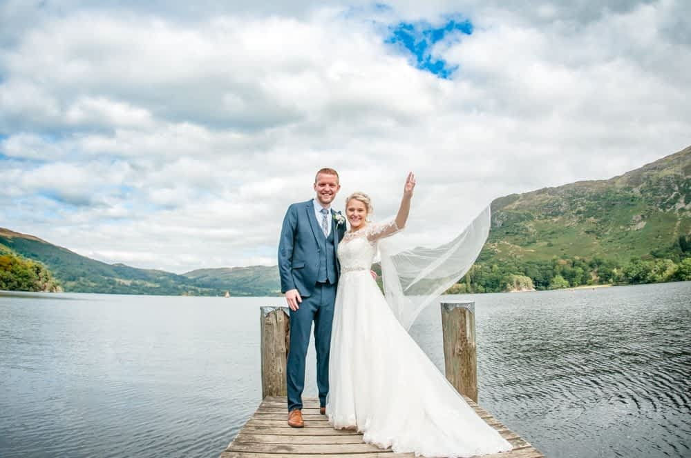 Bride tossing veil in wind, Inn on the Lake Weddings, Lake District