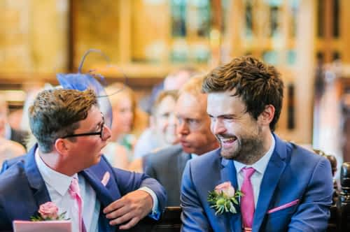 Groom and best man laughing in church, Barnsley wedding photographers