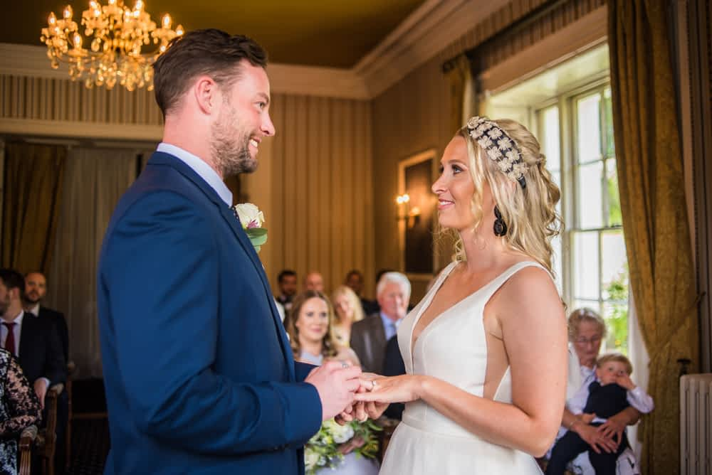 Bride and groom exchanging rings, Overwater Hall wedding, Lake District