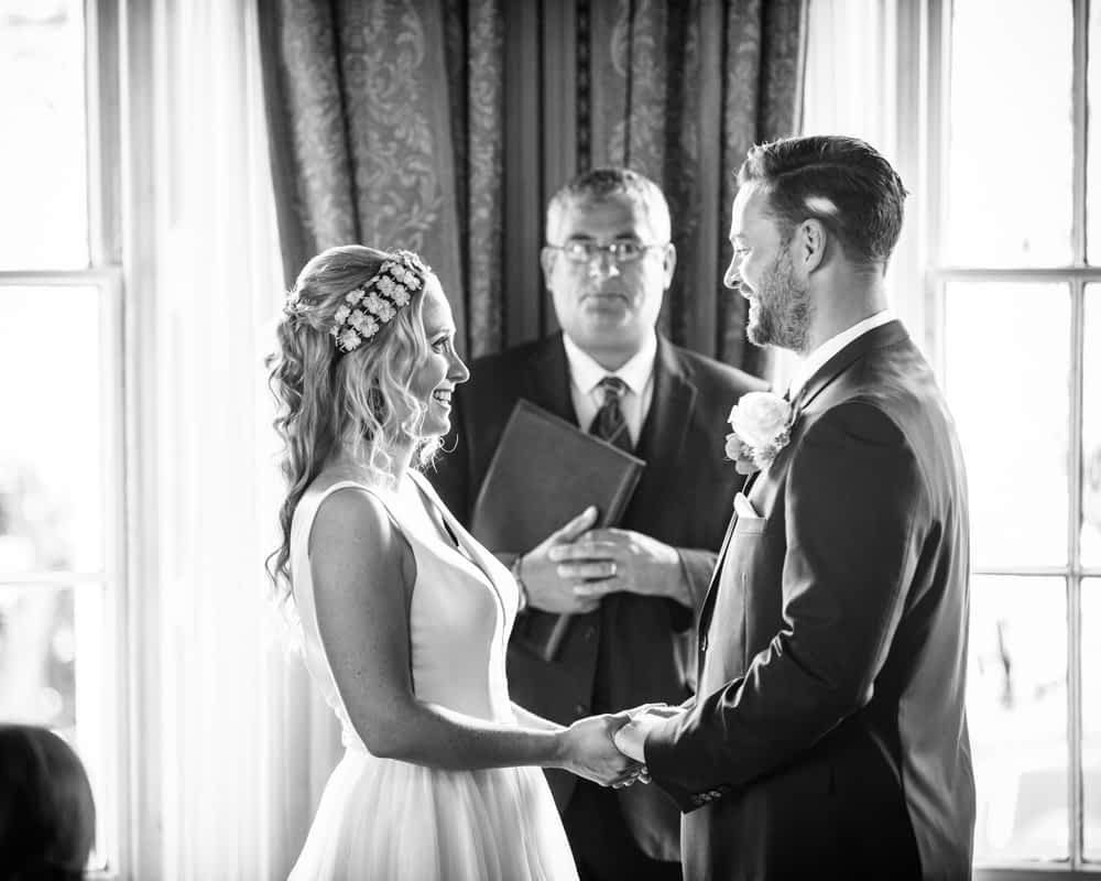 Holding hands during ceremony, Overwater Hall wedding, Lake District