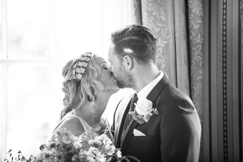 Kissing in ceremony, Overwater Hall wedding, Lake District