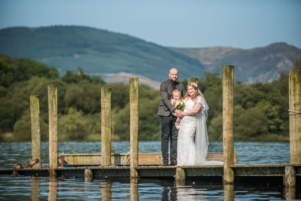 Family standing on jetty on lake, Derwentwater Rock the Dress, Lake District wedding photographer