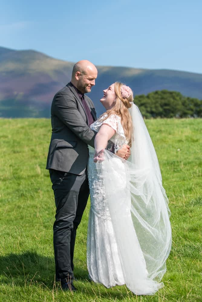 Holding out veil, elopement wedding, Derwentwater Rock the Dress, Lake District wedding photographer
