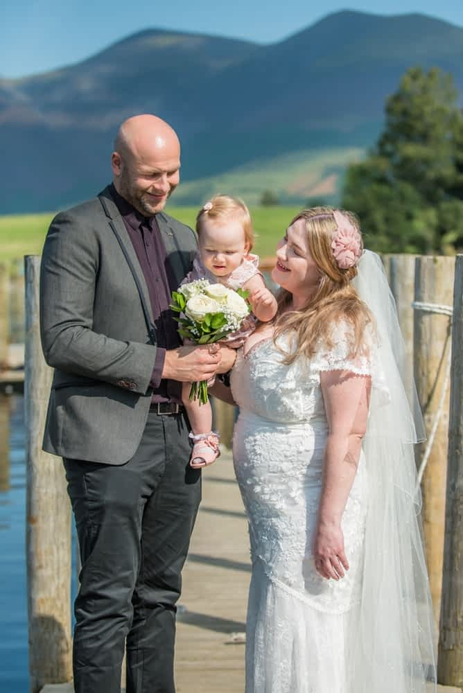 Baby likes the wedding flowers, Derwentwater Rock the Dress, Lake District wedding photographer