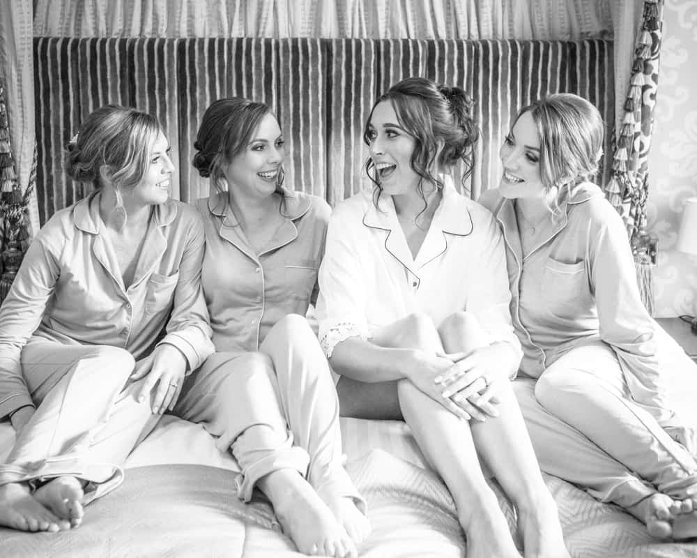Sahra and her bridesmaids laughing on bed, Sheffield wedding photographers, Ringwood Hall Hotel