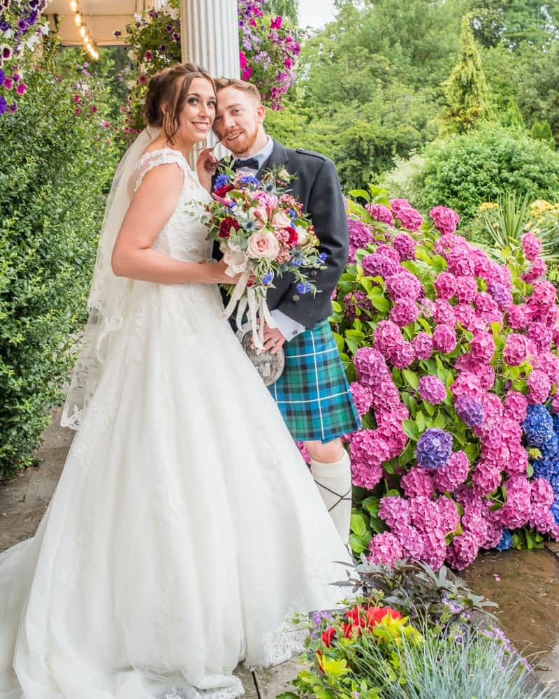 Bride and groom posing by flowers in grounds, Sheffield wedding photographers, Ringwood Hall Hotel