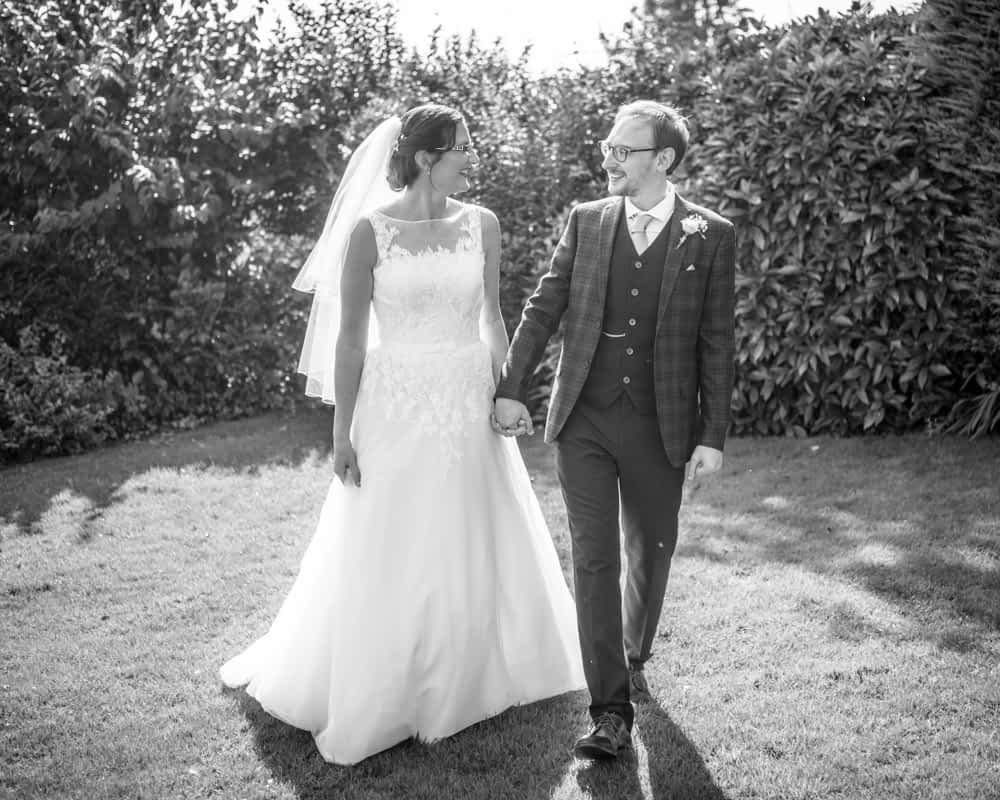 Bride and groom walking in grounds, Shireburn Arms, Lancashire wedding photographers