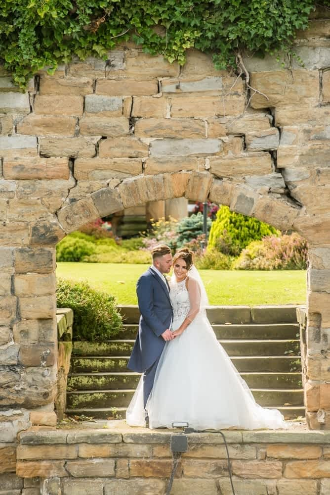 Kisses under the archway, Waterton Park Hotel weddings, Yorkshire wedding photographers