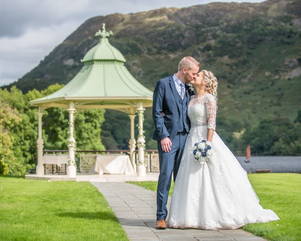Kissing with pagoda in background, Inn on the Lake Weddings, Lake District